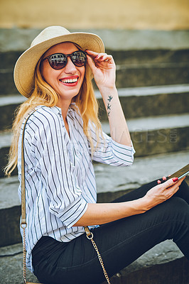 Buy stock photo Shot of a woman using her cellphone while sitting on a staircase in a foreign city