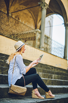 Buy stock photo Shot of a woman using a digital tablet while sitting on a staircase in a foreign city