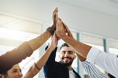 Buy stock photo Cropped shot of a group of businesspeople high fiving in an office