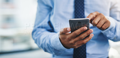 Buy stock photo Cropped shot of an unrecognizable businessman standing alone in the office and using his cellphone to text