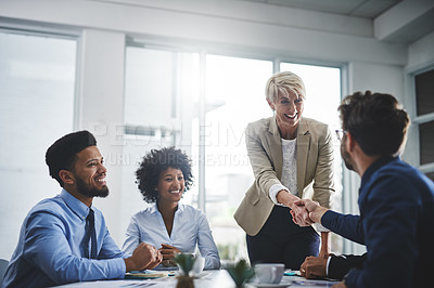 Buy stock photo Cropped shot of a diverse group of businesspeople having a meeting in the office and shaking hands