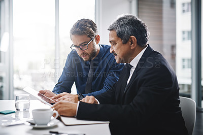 Buy stock photo Cropped shot of two businessmen sitting together and working on a tablet in the office
