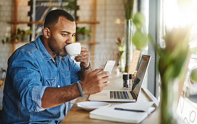 Buy stock photo Cropped shot of a handsome young businessman sitting in a cafe and drinking a cup of coffee while using technology