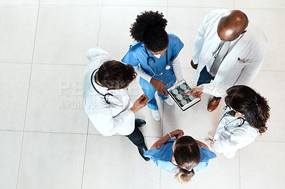 Buy stock photo High angle shot of a team of doctors using a digital tablet to discuss an x ray in a hospital
