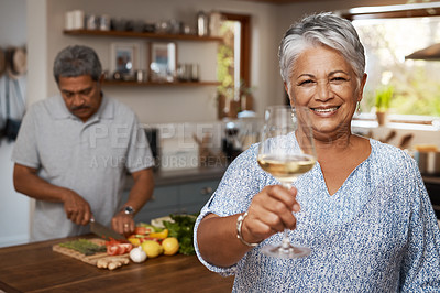 Buy stock photo Portrait of a happy mature woman enjoying a glass of wine while her husband prepares a meal in the background