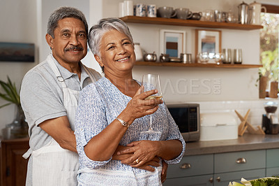 Buy stock photo Portrait of a happy mature couple drinking wine while cooking a meal together at home