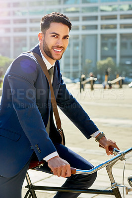 Buy stock photo Portrait of a handsome young businessman riding a bicycle while traveling to work in the city