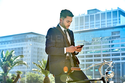 Buy stock photo Shot of a handsome young businessman using a cellphone while riding a bicycle to work in the city