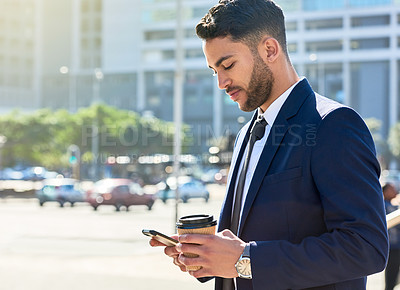 Buy stock photo Shot of a handsome young businessman having coffee and using his cellphone in the city
