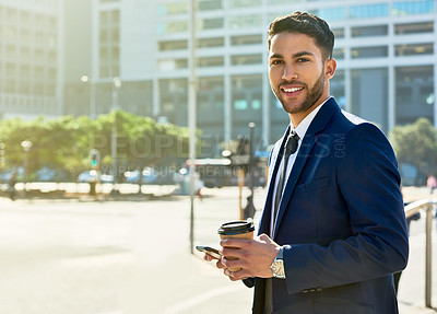 Buy stock photo Portrait of a handsome young businessman having coffee and using his cellphone in the city