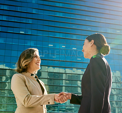 Buy stock photo Shot of two attractive young businesswomen meeting up and shaking hands in the city