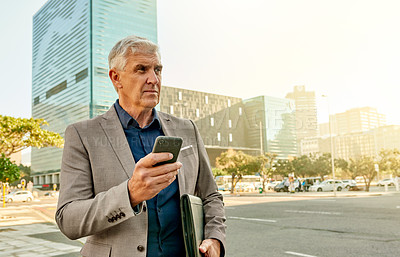 Buy stock photo Shot of a mature businessman using a cellphone while out in the city
