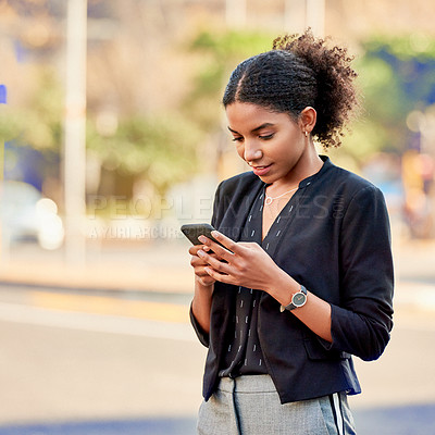 Buy stock photo Shot of an attractive young businesswoman using a cellphone in the city