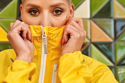 Buy stock photo Cropped portrait of an attractive young woman standing against a tiled wall and covering her mouth with her jacket