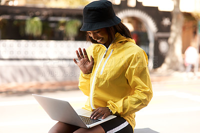 Buy stock photo Shot of an attractive young woman using her laptop to make a video call while relaxing outdoors in the city