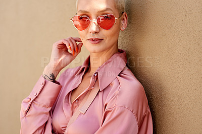 Buy stock photo Cropped portrait of an attractive young woman wearing heart shaped sunglasses and standing against a beige background alone