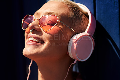 Buy stock photo Cropped shot of an attractive young woman standing against a blue wall and listening to music through headphones