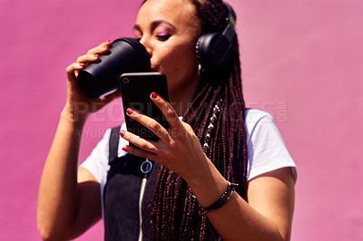 Buy stock photo Cropped shot of an attractive young woman standing against a pink wall alone and drinking coffee while using technology