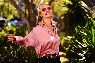 Buy stock photo Portrait of an attractive and stylish young woman wearing sunglasses relaxing in a park outdoors