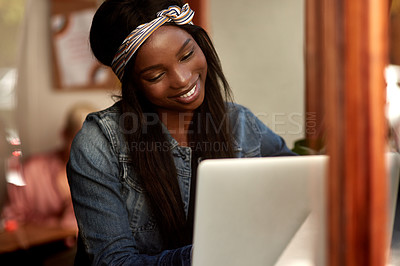 Buy stock photo Shot of an attractive young woman using her laptop while relaxing inside a local cafe