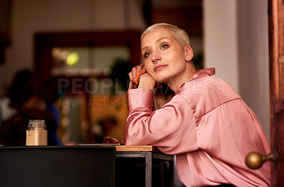 Buy stock photo Shot of an attractive young woman looking thoughtful while relaxing inside a cafe