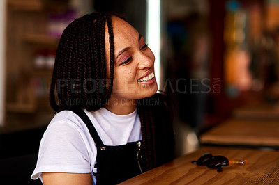 Buy stock photo Shot of an attractive and happy young woman relaxing inside a local cafe