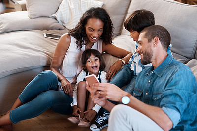 Buy stock photo Shot of a family of four watching something on a cellphone