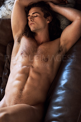 Buy stock photo High angle shot of a muscular young man sleeping naked on his couch at home