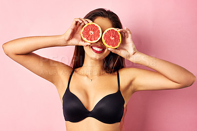 Buy stock photo Studio shot of a beautiful young woman holding grapefruit slices in front of her eyes against a pink background