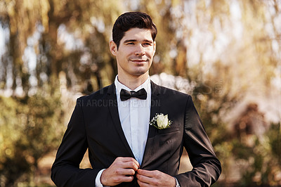 Buy stock photo Cropped shot of a handsome young bridegroom adjusting his suit while preparing for his wedding outdoors