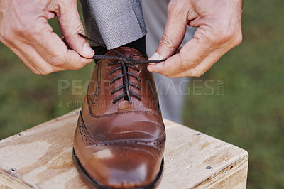 Buy stock photo Cropped shot of an unrecognizable mature bridegroom adjusting his shoelaces while preparing fir his wedding outdoors