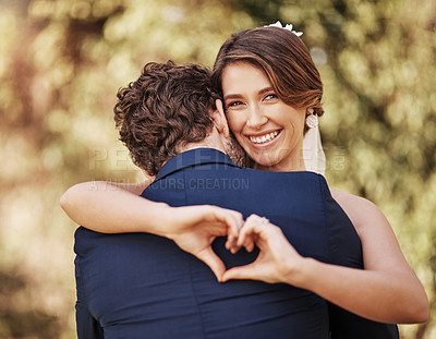Buy stock photo Cropped shot of an affectionate young bride smiling while making a heart shape on her groom's back on their wedding day