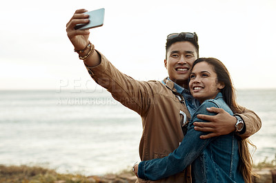Buy stock photo Shot of a happy young couple taking selfies on a vacation along the coast