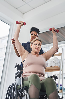 Buy stock photo Shot of a young physiotherapist helping her wheelchair bound patient exercise with dumbbells at a clinic