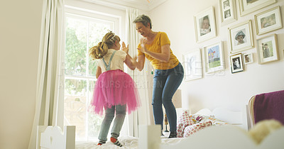 Buy stock photo Shot of a senior woman having fun with her granddaughter at home