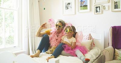 Buy stock photo Shot of a senior woman taking selfies with her granddaughter while playing dress up at home