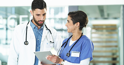 Buy stock photo Cropped shot of a handsome young male doctor using a digital tablet with a female nurse while standing in a hospital