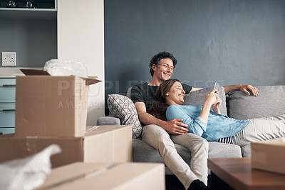 Buy stock photo Shot of a couple using a cellphone while moving house