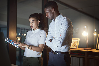 Buy stock photo Cropped shot of two young businesspeople using a digital tablet together while working late in a modern office