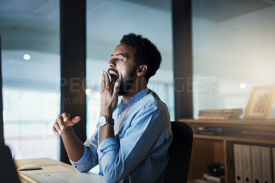 Buy stock photo Shot of a young businessman yawning while working on a computer in an office at night