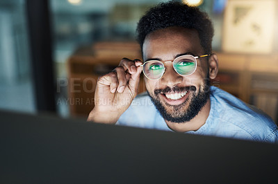 Buy stock photo Portrait of a young businessman working on a computer in an office at night