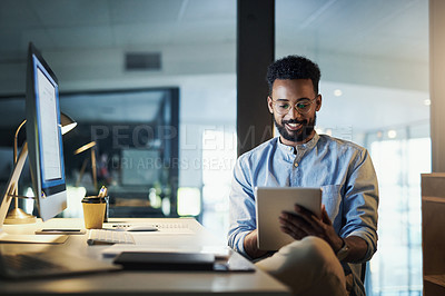 Buy stock photo Shot of a young businessman using a digital tablet in an office at night