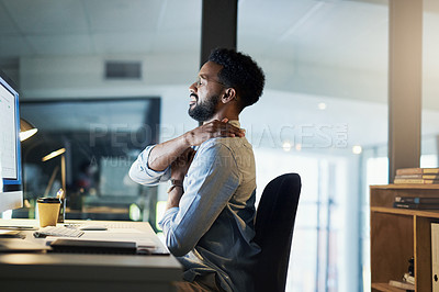 Buy stock photo Shot of a young businessman experiencing neck pain while working in an office at night