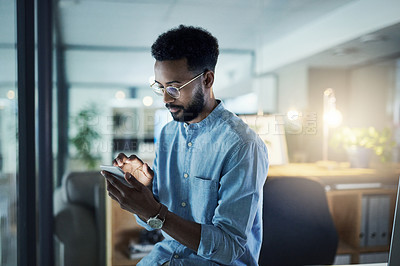 Buy stock photo Shot of a young businessman using a cellphone in an office at night