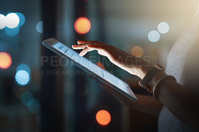 Buy stock photo Cropped shot of an unrecognizable businesswoman using a digital tablet while working late