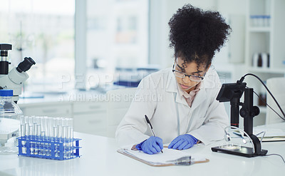 Buy stock photo Cropped shot of an attractive young female scientist making notes while working with a digital microscope in a laboratory