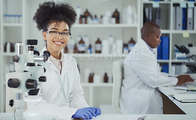 Buy stock photo Cropped portrait of an attractive young female scientist smiling while working in a laboratory with her colleague in the background