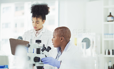 Buy stock photo Cropped shot of two attractive young female scientists using a microscope while working together in a laboratory