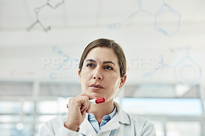 Buy stock photo Shot of a young scientist looking at the notes written on a glass wall in a lab