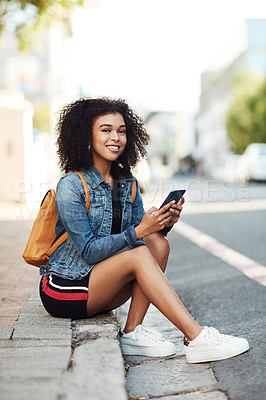 Buy stock photo Full length shot of an attractive young woman sitting down on a sidewalk and using her cellphone in the city